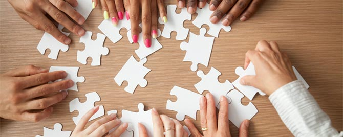 photo - closeup of multiple people working together on a puzzle